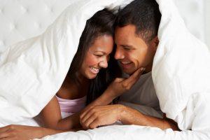 casal praticando gouinage na cama